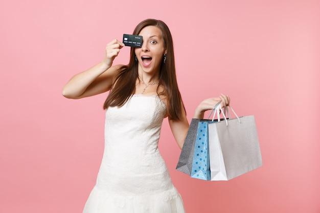 Conmocionada mujer divertida en vestido blanco que cubre los ojos con tarjeta de crédito, sosteniendo bolsas de paquetes multicolores con compras después de ir de compras