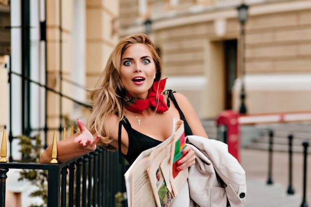 Conmocionada mujer rubia discutiendo las últimas noticias sosteniendo el periódico