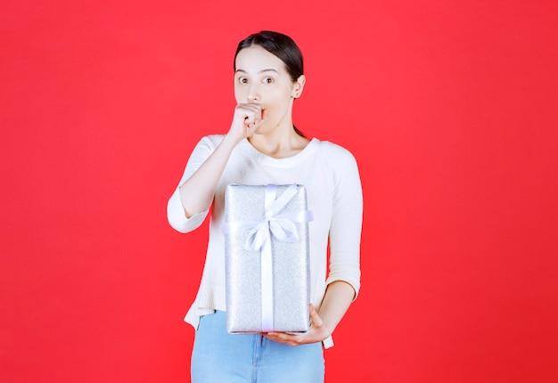 Conmocionada mujer sosteniendo caja de regalo en la pared roja