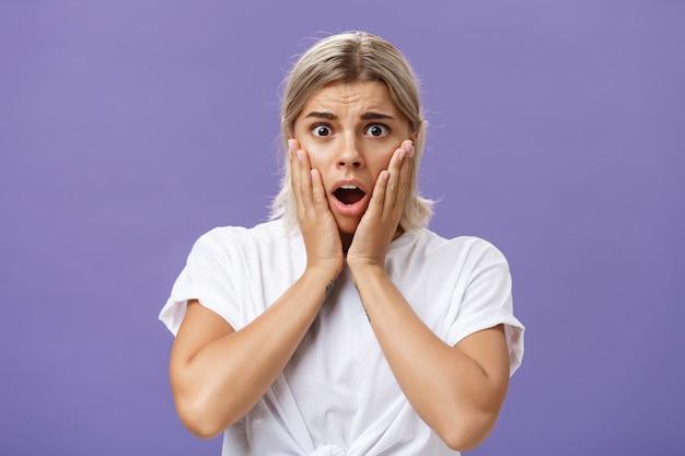 Conmocionada y preocupada mujer europea tonta que expresa empatía sintiendo pena por el pobre animal en peligro jadeando abriendo la boca tomados de la mano en la cara frunciendo el ceño sintiéndose preocupado por la pared púrpura