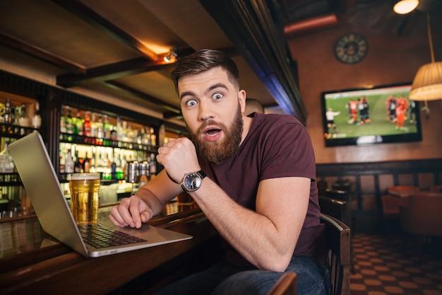 Conmocionado asombrado joven bebiendo cerveza y usando la computadora portátil en el bar