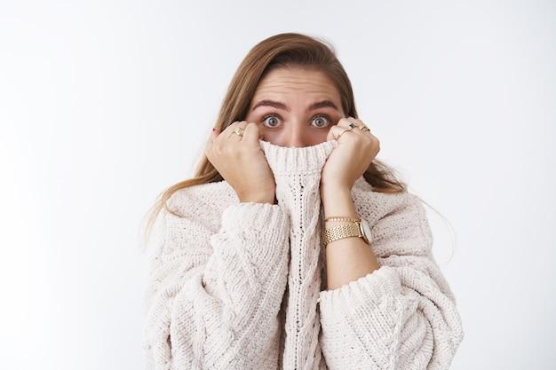 Conmocionado asustado aturdido linda mujer caucásica escondiendo suéter de cuello de cara tirando de tela nariz ensanchar los ojos asombrado sin palabras asustado viendo horror de pie aturdido fondo blanco, asustado