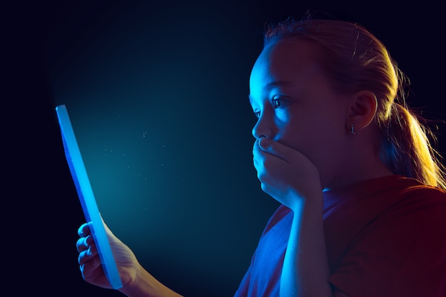 Conmocionado, asustado. retrato de niña caucásica sobre fondo oscuro de estudio en luz de neón. modelo femenino hermoso que usa la tableta. concepto de emociones humanas, expresión facial, ventas, publicidad, tecnología moderna, gadgets.