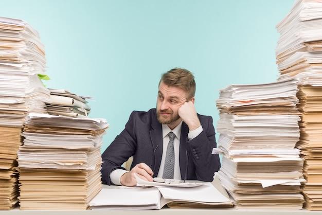 Conmocionado empresario sentado a la mesa con muchos papeles en la oficina