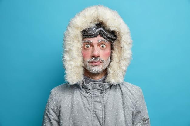 Conmocionado hombre adulto congelado mira fijamente tiene ojos aparecieron cara roja congelada durante el clima helado