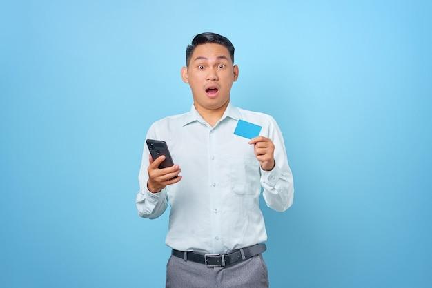 Conmocionado joven empresario guapo sosteniendo smartphone y tarjeta de crédito sobre fondo azul.