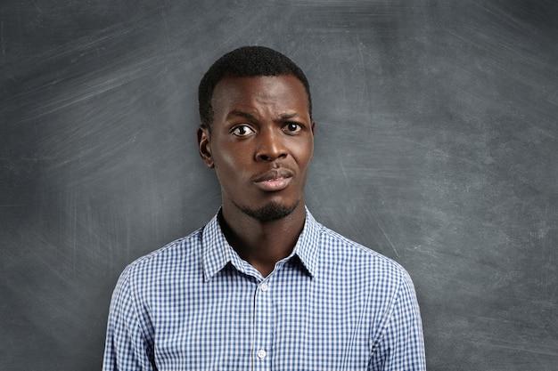 Conmocionado maestro de piel oscura sorprendido por la mala conducta de sus alumnos durante su primer día en la escuela.
