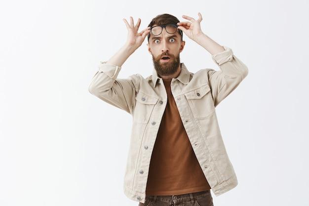 Conmocionado y sorprendido hombre barbudo con gafas posando contra la pared blanca