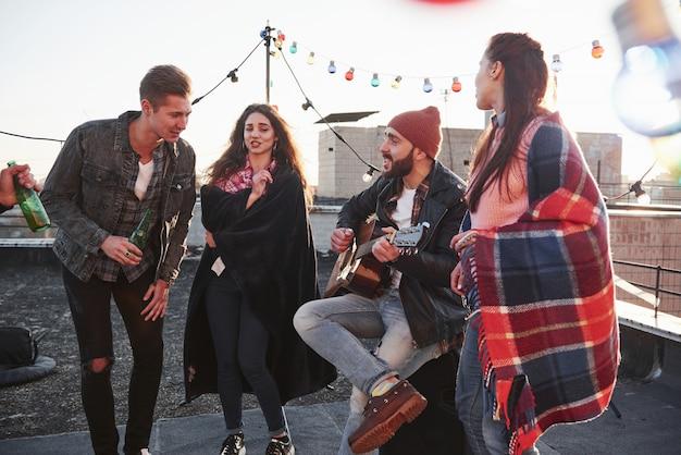 Conmovedora pieza de arte musical. fiesta en la azotea con alcohol y guitarra acústica en un soleado día de otoño