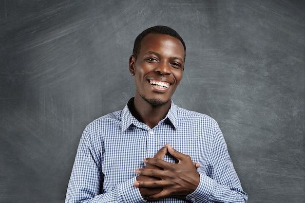Conmovido y agradecido hombre africano sonriendo felizmente, tomados de la mano sobre su pecho para expresar su gratitud y agradecimiento. hombre de piel oscura que parece satisfecho con una historia conmovedora y penetrante
