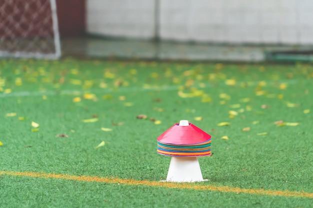 Cono deportivo colorido y marcador para fútbol y otros entrenamientos deportivos en un campo de hierba de pradera