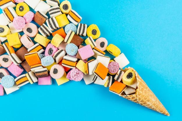 Cono de galleta con caramelos de regaliz de colores sobre fondo azul claro
