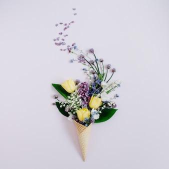 Cono de galleta con flor lila, lirio de los valles, ramo de tulipanes