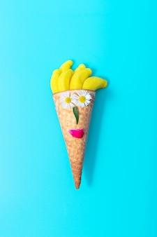 Cono de galleta de helado y caramelos de mermelada sobre un fondo azul, fondo creativo de verano.