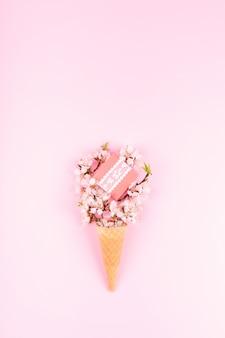 Cono de galleta de helado con flores de colores y caja de regalo en rosa
