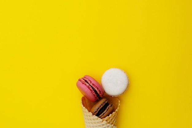 Cono de galleta de helado con macarrones sobre fondo amarillo. endecha plana, postre.