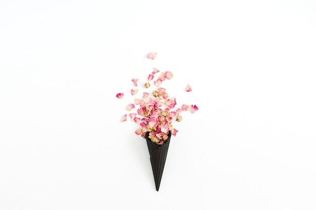 Cono de galleta de helado negro con pétalos de rosas rosadas secos aislados en blanco