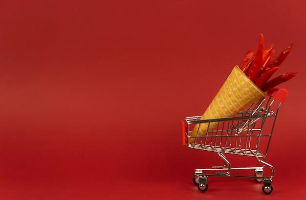 Un cono de galleta lleno de chiles rojos picantes se encuentra en un carrito de la compra sobre un fondo rojo.