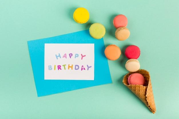 Cono de galleta con macarrones cerca de la tarjeta de feliz cumpleaños sobre fondo verde menta