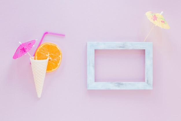 Cono de galleta con naranja, paja y sombrilla cerca del marco