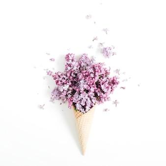 Cono de galleta con ramo de flores lilas sobre blanco