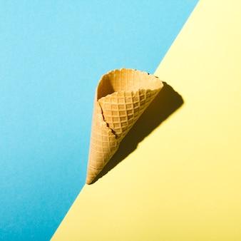 Cono de galleta sobre fondo azul y amarillo