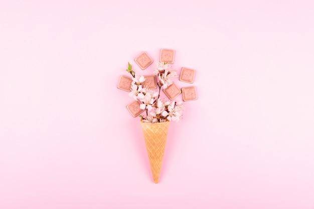 Cono de gofre de helado con flores de colores y chocolate rosa sobre rosa