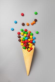 Cono de helado con dulces multicolores sobre fondo gris