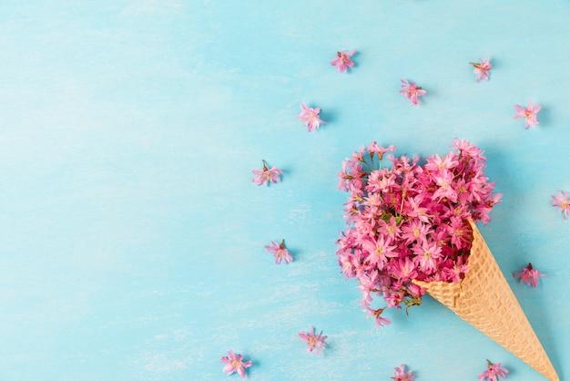 Cono de helado con flor de primavera rosa cereza o sakura flores con espacio de copia. aplanada