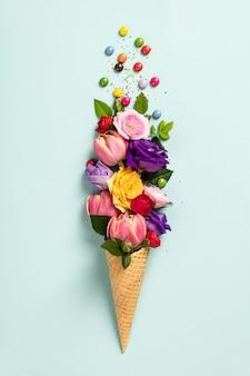 Cono de helado con flores y rocía concepto mínimo de verano.