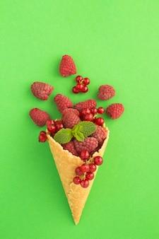 Cono de helado con frambuesas y grosellas rojas