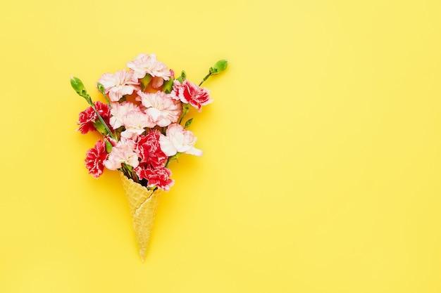 Cono de helado de galleta con flores de clavel rojo y rosa sobre fondo amarillo copia del concepto de verano