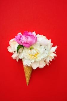 Cono de helado de galleta con flores de peonía blanca y rosa sobre fondo rojo.