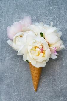 Cono de helado de galleta con flores de peonía blanca sobre gris.