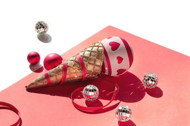 Cono de helado de gofre dorado con adornos navideños blancos y rojos, bolas de discoteca y cintas sobre papel naranja