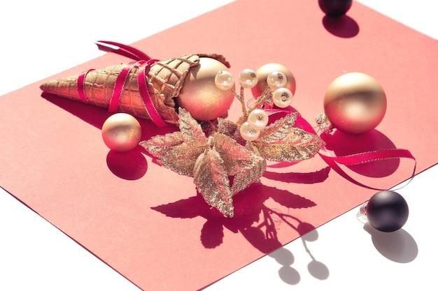 Cono de helado de gofre dorado con adornos navideños dorados y negros, bayas, estrellas y cintas rojas sobre papel naranja