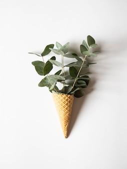 Cono de helado de gofres con ramitas de eucalipto verde