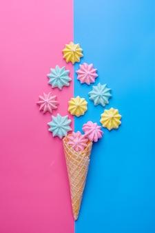 Cono de helado con merengues en azul y rosa.