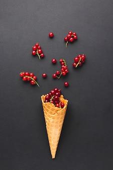 Cono de helado plano con grosellas rojas.