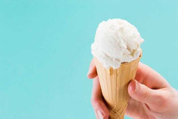 Cono de helado de vainilla blanco en la mano
