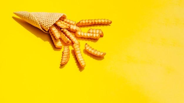 Cono con papas fritas sobre fondo amarillo