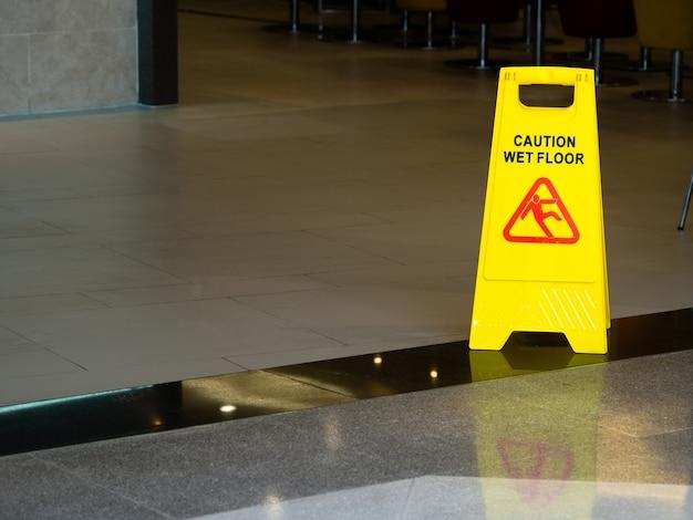 Cono de plástico amarillo con cartel que muestra advertencia de suelo mojado en restaurante en grandes almacenes