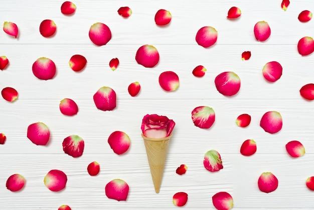 Cono con rosa en medio de pétalos