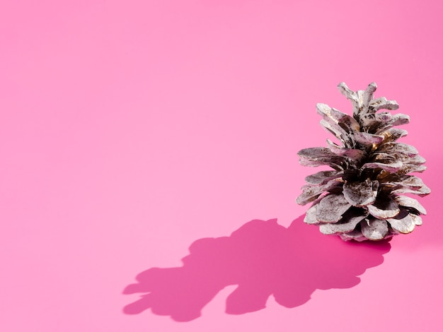 Cono con sombra sobre fondo rosa