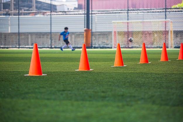 Cono de tácticas de balón de fútbol en campo de hierba con antecedentes de formación formación de niños en fútbol