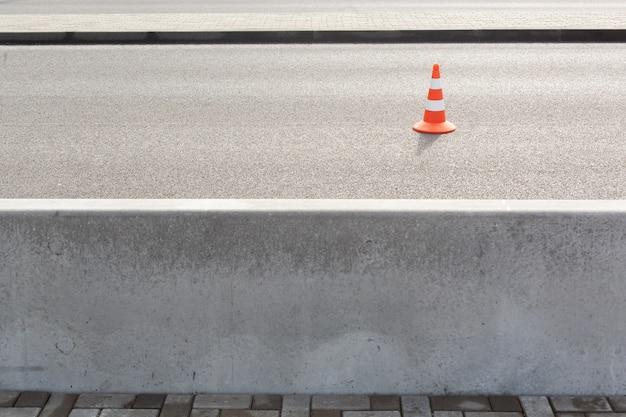 Cono de tráfico sobre pavimento bituminoso para coches con una gran valla de hormigón que separa la carretera y la acera