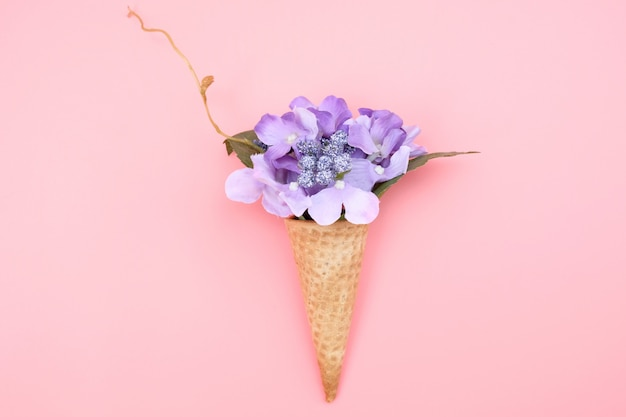 Cono de waffle con flores sobre fondo rosa