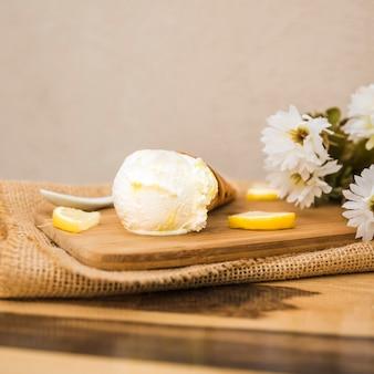Cono de waffle con helado cerca de rebanadas de frutas y flores frescas