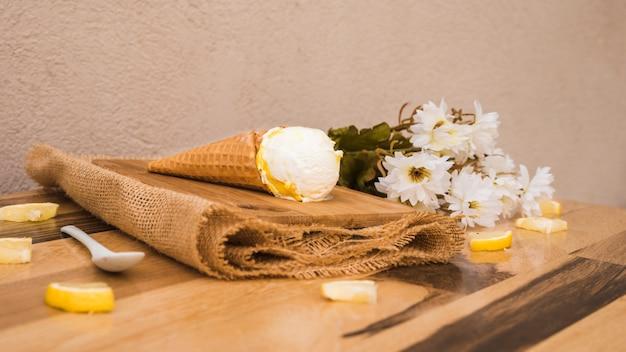 Cono de waffle con helado cerca de rodajas de frutas frescas y flores en la servilleta