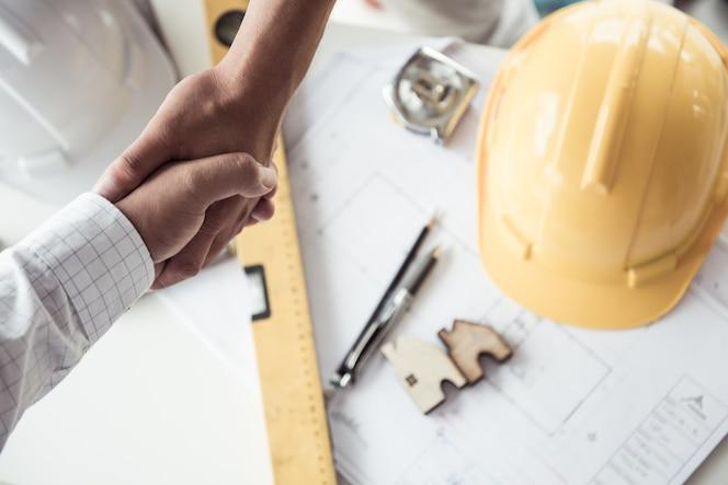 Conocer al equipo de ingenieros que trabajan en un proyecto de construcción en la mesa. vista superior